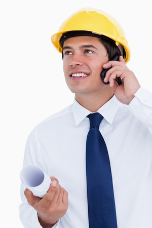 Close up of smiling architect talking on his cellphone against a white background photo