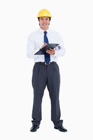 Smiling male architect with pen and clipboard against a white background photo