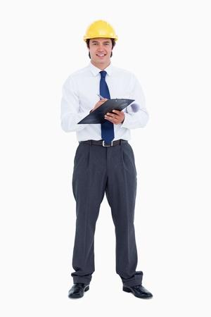 supervisores: Sonriendo arquitecto masculina con la pluma y el portapapeles sobre un fondo blanco