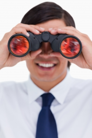 Close up of smiling tradesman looking through binoculars against a white background photo