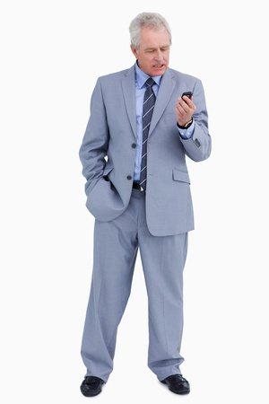 Mature tradesman looking angry at his cellphone against a white background photo