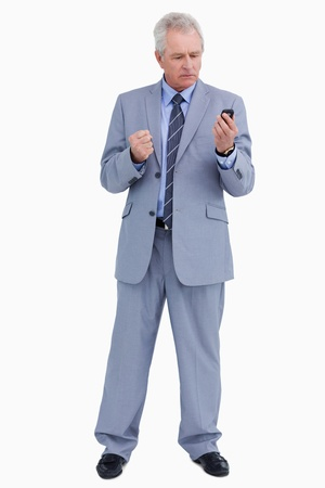 Mature tradesman giving his cellphone an angry look against a white background photo