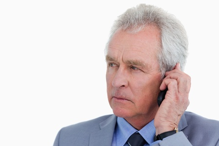 caller: Close up of mature tradesman listening to caller against a white background Stock Photo