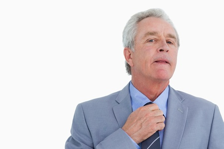 Close up of mature tradesman adjusting tie against a white background