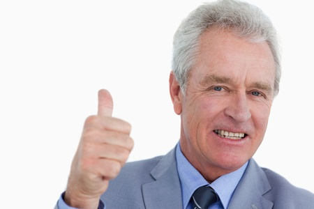 Close up of smiling mature tradesman giving approval against a white background