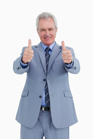 good work: Smiling mature tradesman giving his thumbs up against a white background