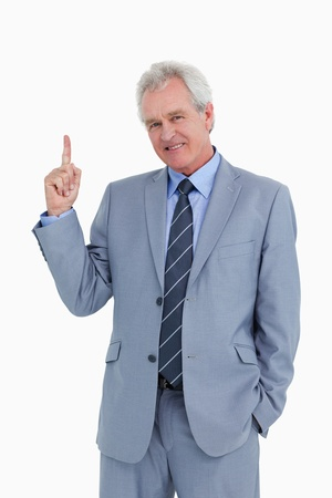 Smiling mature tradesman pointing up against a white background photo