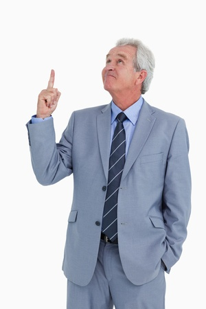 Mature tradesman pointing and looking up against a white background photo