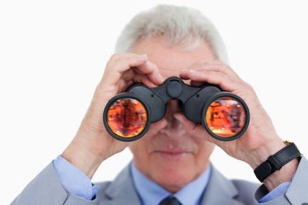 Close up of mature tradesman looking through spy glass against a white background photo