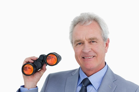 Close up of smiling mature tradesman with spy glass against a white background photo