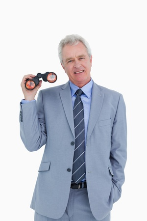 Smiling mature tradesman with spy glass against a white background Stock Photo - 13653372