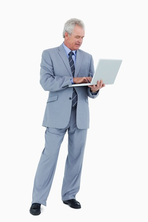 Mature tradesman working on his laptop against a white background photo