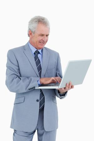 business man laptop: Comerciante sonriendo madura trabajando en su computadora port�til sobre un fondo blanco Foto de archivo