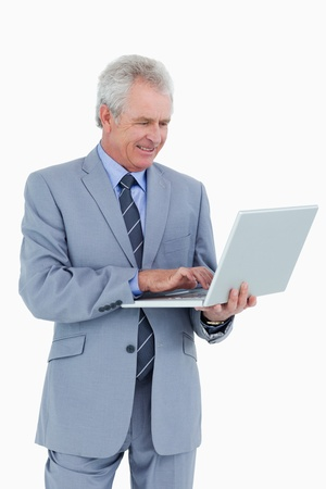 Smiling mature tradesman working on his laptop against a white background photo
