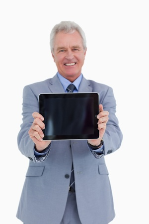 Smiling mature tradesman presenting screen of his tablet computer against a white background photo