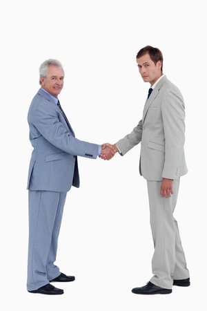 Side view of tradesmen closing a deal against a white background photo