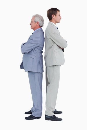 Side view of serious tradesmen standing back to back against a white background photo