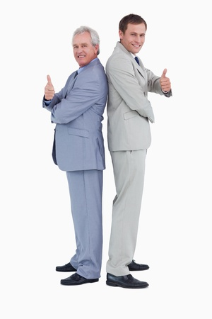 Tradesmen standing back to back giving thumbs up against a white background photo