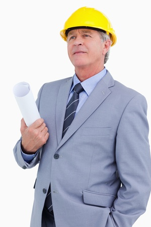 Mature architect wearing helmet and holding plans against a white background photo