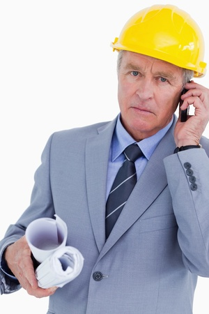 Serious mature architect on his cellphone against a white background photo