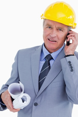 Mature architect talking on his cellphone against a white background photo
