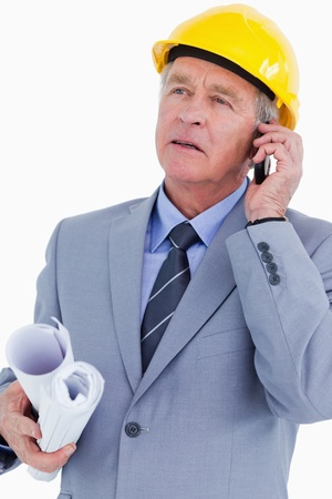 Mature architect on his mobile phone against a white background photo