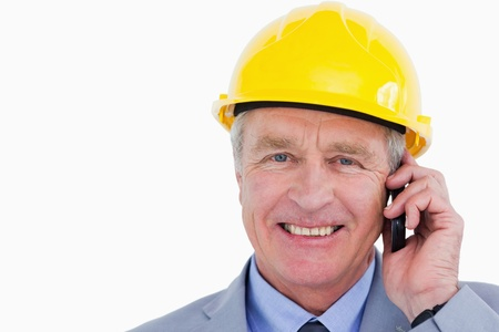 Smiling mature architect on the phone against a white background photo