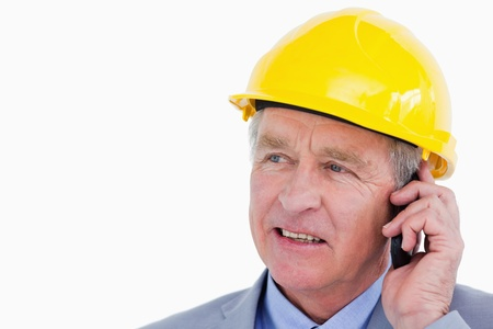 Close up of mature architect on the phone against a white background photo