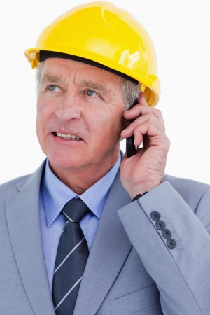 Close up of mature architect talking on the phone against a white background photo