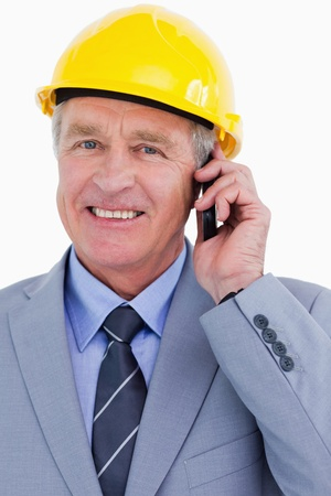 Close up of smiling mature architect on his cellphone against a white background photo