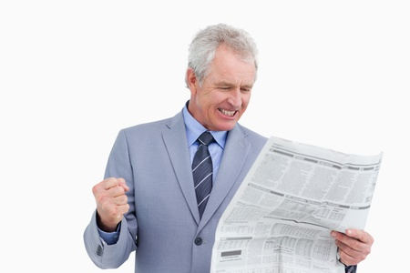 Mature tradesman cheering about news paper article against a white background photo