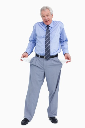 Clueless tradesman showing his empty pockets against a white background photo