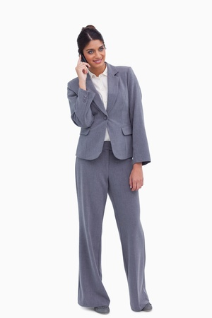 Smiling female entrepreneur having a conversation on the phone against a white background photo