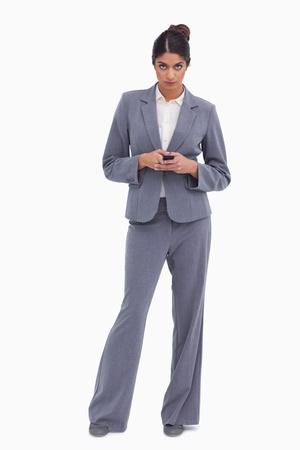 Female entrepreneur holding cellphone against a white background