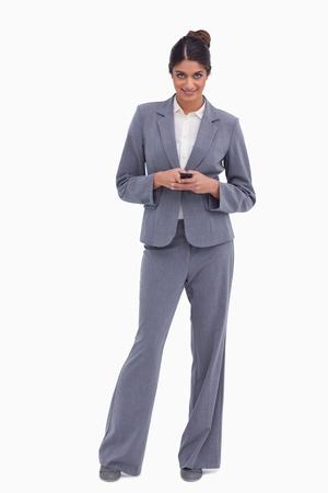 Smiling female entrepreneur holding cellphone against a white background photo