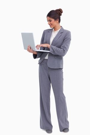 Smiling female entrepreneur working on her laptop against a white background photo