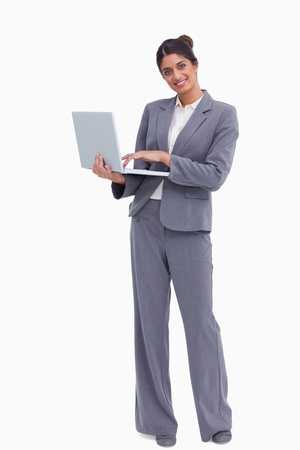 Smiling female entrepreneur with her laptop against a white background photo