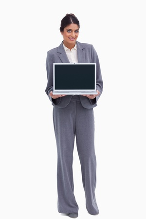 Smiling female entrepreneur presenting screen of her laptop against a white background photo