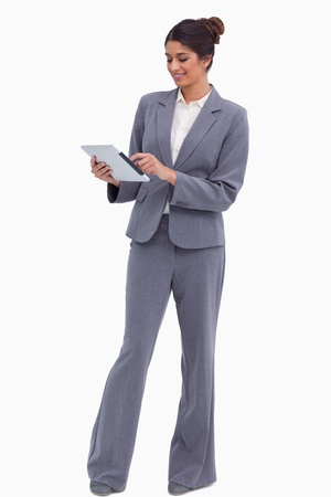 Smiling female entrepreneur working on her tablet computer against a white background photo