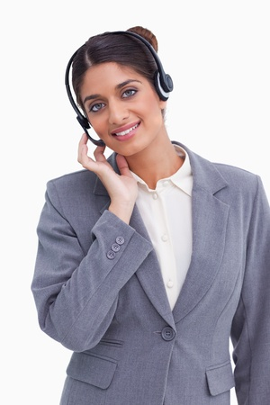 Smiling female call center agent adjusting her headset against a white background photo