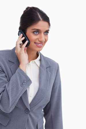 Smiling female entrepreneur on her mobile phone against a white background photo