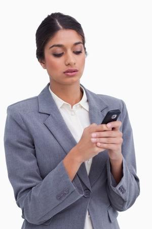 Female entrepreneur writing text message on her cellphone against a white background photo