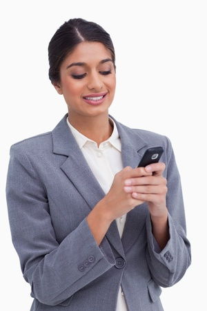 Smiling female entrepreneur writing text message against a white background photo