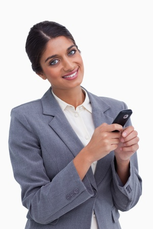 Smiling female entrepreneur with her cellphone against a white background photo