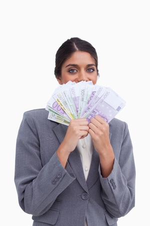 Female entrepreneur hiding her face behind bank notes against a white background photo