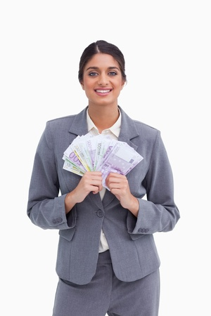 Smiling female entrepreneur with bank notes against a white background photo