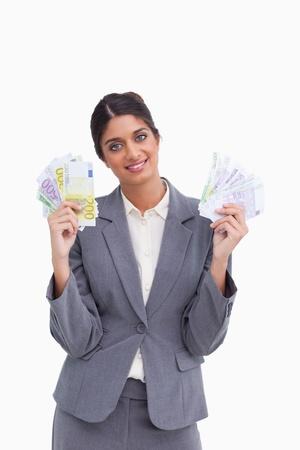 Smiling female entrepreneur holding bank notes against a white background photo