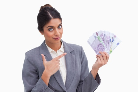 Female entrepreneur pointing at money in her hand against a white background photo