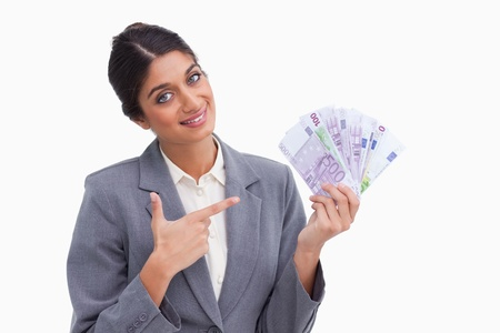 Smiling female entrepreneur pointing at money in her hand against a white background photo