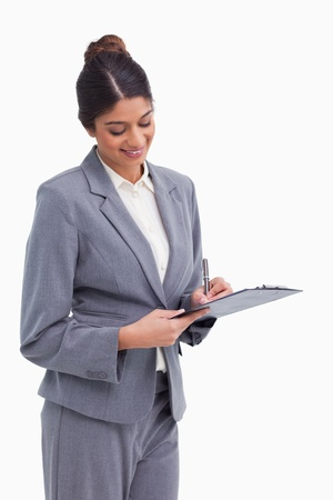 Smiling female entrepreneur taking notes on clipboard against a white background photo
